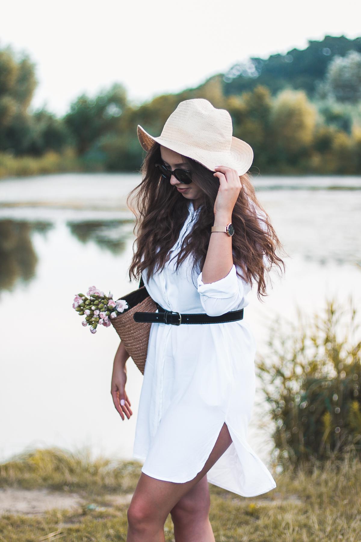 Biała sukienka w wakacyjnej stylizacji ze słomianym koszykiem